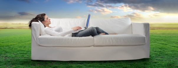 Young woman lying on a sofa on a green meadow and using a laptop